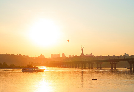 Skyline of Kiev with Mother Motherland monument and Paton bridge at sunset. Ukraine