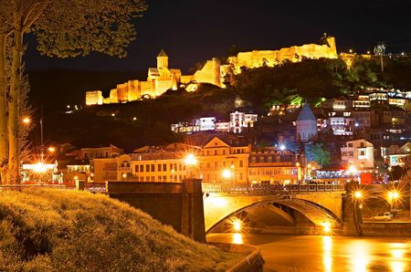 towns: Tbilisi Old Town with famous Narikala castle on a hill at night