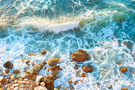 tides: Waves on a rocky beach at sunset. Aerial view Stock Photo