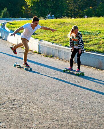 """alegria: KIEV, Ucrania - DIC 10, 2015: pareja joven que monta los longboards abajo de la colina al atardecer en un parque. Longboard es un tipo de equipamiento deportivo algo similar a una tabla de skate, pero en cierto modo """"más largo"""". Editorial"""