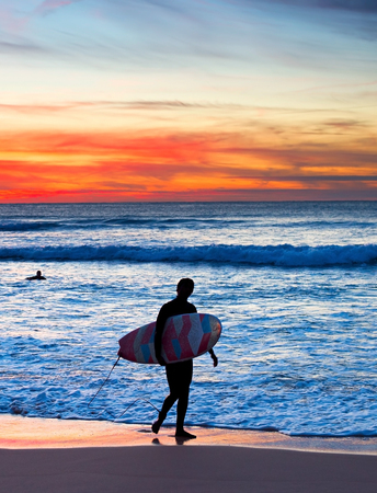 unrecognizable: Surfer with surfboard walking on the beach