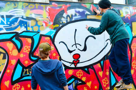 vandal: LISBON, PORTUGAL - DECEMBER 23, 2014: Boys painting graffiti on the wall in Lisbon.Along with London, Berlin, New York and others, Lisbon is one of the worlds great cities for graffiti and street art Editorial