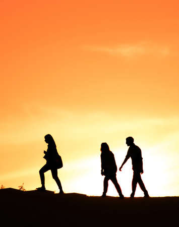 three person: Three person walking at sunset on a hill Stock Photo