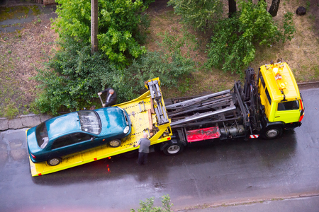 Loading broken car on a tow truck on a road. Aerial view Standard-Bild