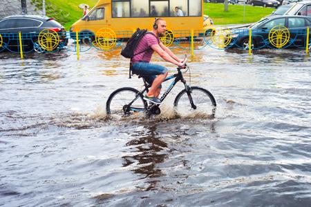 KIEV, UKRAINE - MAY 25, 2016: Man riding bicycle on the flooded city road in Kiev. Kiev is the capital of Ukraine.
