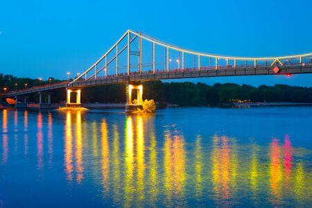 Pedestrian bridge over river Dnipro at twilght in Kyiv, Ukraine. Stock Photo