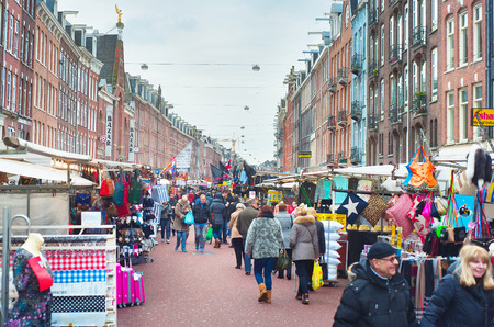 AMSTERDAM, NETHERLANDS - FEB 14, 2014: People at Albert Cuyp Market in Amsterdam. The market began trading in 1904, now over 300 stalls are lining both sides of the Albert Cuyp street.