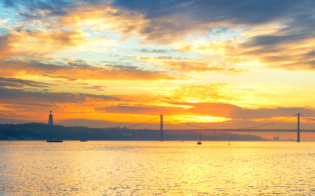 the tagus: Tagus river, Christ the King statue and 25 April bridge at sunset. Lisbon, Portugal Stock Photo