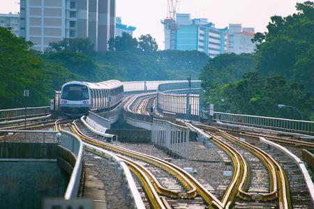Singapore MRT train on a railroad at sunset Foto de archivo