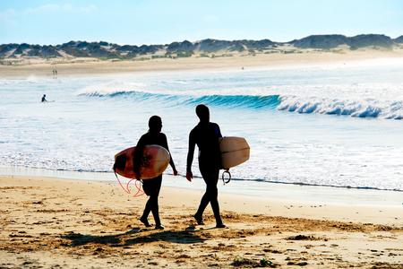 オーシャン ・ ビーチの上を歩くサーファー夫婦