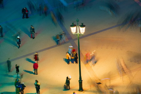 People under a lantern. Long exposure. Motion blur
