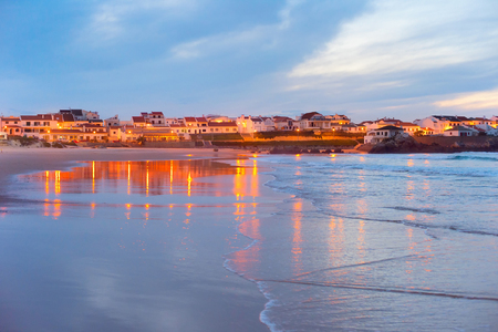 water town: Town on the ocean shore reflected in the water at twilight. Baleal, Portugal