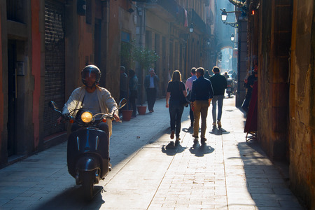 BARCELONA, SPANIEN - NOV 04, 2016: Menschen gehen und reiten Roller auf der Altstadt von Barcelona. Barcelona ist die fünftgrößte Stadt Europas nach London, Paris, Istanbul und Rom