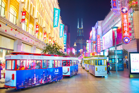 SHANGHAI, CHINA - DEC 28, 2016: Tourists trams on Nanjiing road in Downtown of Shanghai. The area is the main shopping district of the city and one of the worlds busiest shopping streets. Editorial