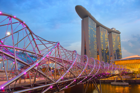 SINGAPORE - JAN 13, 2017: Helix bridge and Marina Bay Sands Resort at twilight in Singapore. Marina Bay as the world's most expensive standalone casino property at S$8 billion