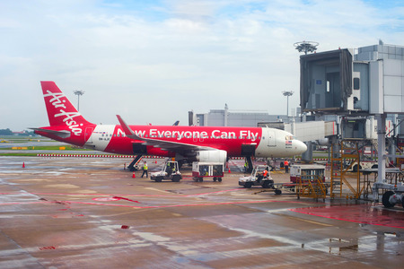 SINGAPORE - FEB 15, 2017: AirAsia aircraft in Changi International Airport during unloading baggage. Changi is the biggest airport in the world.