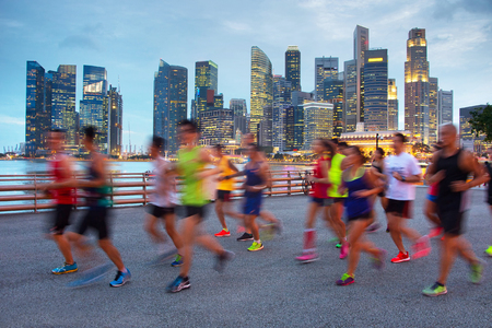 Group of runners on Singapore quayside at twilight