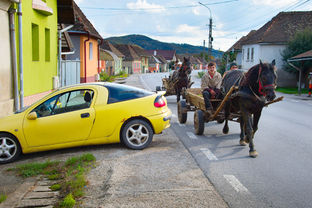 DANES, ROMANIA - OCTOBER 05, 2016: Locals driving horse cart on a road in a small Romanian village. The Romanian government claims that 10% of road accidents are caused by horse carts