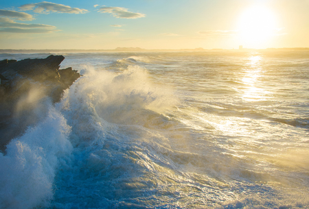Wave crashing of a rocky beach at sunset. Portugal