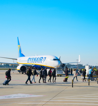 PORTO, PORTUGAL - DEC 25, 2016: Passengers boarding Ryanair aiplane at Francisco Sa Carneiro Airport. The airport is currently the second-busiest in the country, based on aircraft operations