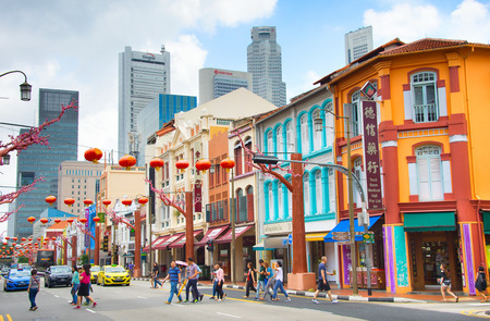 SINGAPORE - FEB 17, 2017: People crossing the road in Chinatown of Singapore. Modern skyscrapers of Singapore Downtown on a background. 에디토리얼
