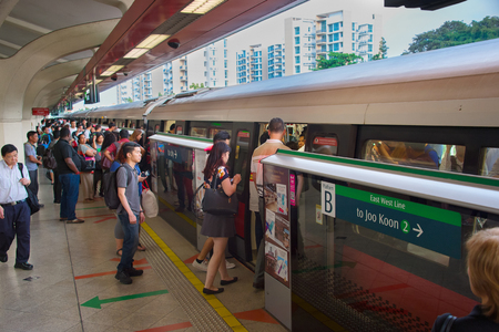 go inside: SINGAPORE - JAN 13, 2017: Passengers in Singapore Mass Rapid Transit (MRT) train. The MRT has 102 stations and is the second-oldest metro system in Southeast Asia Editorial