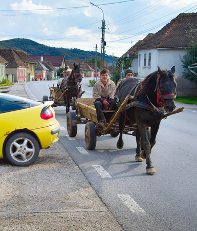 carreta madera: DANES, ROMANIA - OCTOBER 05, 2016: Locals driving horse cart on a road in a small Romanian village. The Romanian government claims that 10% of road accidents are caused by horse carts