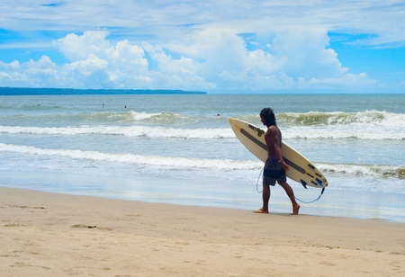 CANGGU, BALI ISLAND, INDONESIA - JAN 19, 2017: Local surfer walking with surfboard on the beach. Bali island is one of the worlds best surfing destinations Editorial