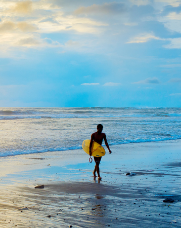 Surfer walking on the beach with surfboard at sunset. Bali island, Indonesia