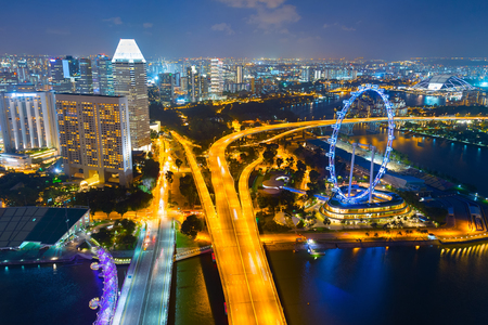 Skyline of Singapore with famous Singapore Ferries Wheel at twilight Editorial