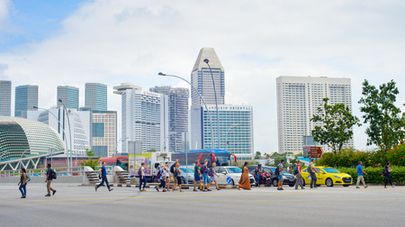 SINGAPORE - JAN 14, 2017: People crossing the road in Singapore. Singapore is a global commerce, finance and transport hub Editorial