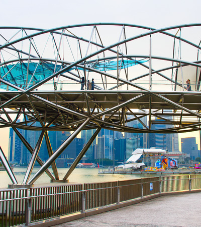 SINGAPORE - JAN 14, 2107: People walking by the Helix Bridge in Singapore. The Helix is fabricated from 650 tonnes of Duplex Stainless Steel and 1000 tonnes of carbon steel.