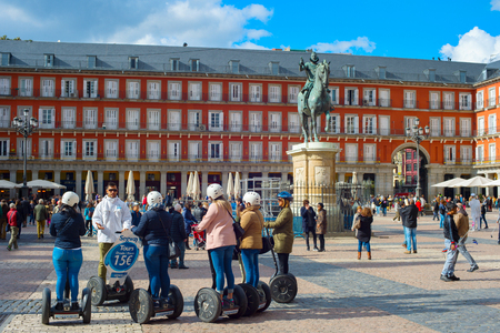 MADRID, SPAIN - NOV 07, 2016: Group of tourist on Segway on a Mayor Plaza in front of the statue of King Philips III in Madrid
