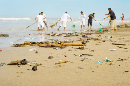 Mensen schoonmaken vuilnis vervuild met afval oceaan strand. Bali eiland, Indonesië Stockfoto