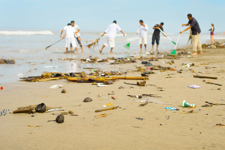 People cleaning trashy polluted with garbage ocean beach. Bali island, Indonesia Foto de archivo