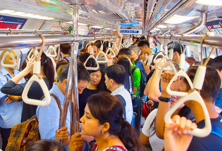 SINGAPORE - JAN 13, 2017: Passengers in Singapore Mass Rapid Transit (MRT) train. The MRT has 102 stations and is the second-oldest metro system in Southeast Asia Sajtókép