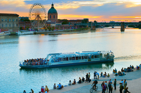 TOULOUSE, FRANCE - AUG 13, 2107: People at the embankment of Toulouse at sunset. Toulouse is a city in southwestern France, near the Pyrenees, capital of Haute-Garonne in the Midi-Pyrenees region Editorial