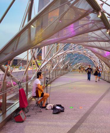SINGAPORE - JAN 13, 2017: Street musician playing guitar on Helix bridge in Singapore. Helix bridge is a bridge in the Marina Bay. Editorial