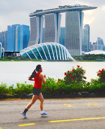 SINGAPORE - FEB 16, 2017: Beautiful young chinese woman running in Singapore bay at sunset. Motion blur.