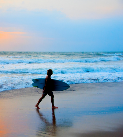 Dreadlocks surfer on the beach with surfboard . Bali island Stock Photo