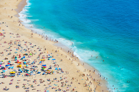 Crowded  ocean beach in a bright summer sunny day. Nazare, Portugal