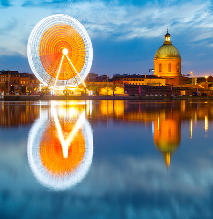 Twilight view of Hospital de La Grave and Ferries Wheel reflected in Garone river. Toulouse, France