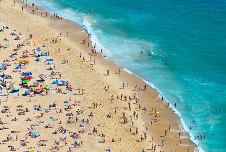 Crowd of people at the  ocean beach in a bright summer sunny day. Nazare, Portugal