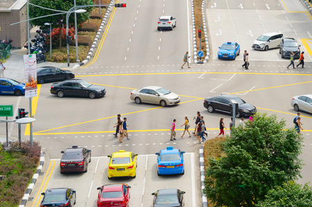 SINGAPORE - FEB 18, 2017: People crossing a road in Singapore. Singapore is a major financial, business and cultural city in Southeast Asia