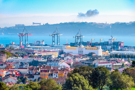 Skyline of Lisbon with freight cranes and cargo containers in port by Tagus river, silhouette of Almada bank on background