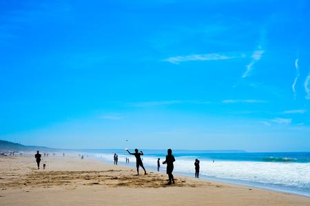 People playing beach racket at Costa da Caparica beach. Lisbon, Portugal