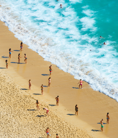 People at  ocean beach in a summer sunny day. Nazare, Portugal Standard-Bild