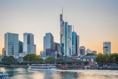 Sunset sky over city embankment, touristic boats and bridge by Frankfurt-am-Main skyline with modern architecture, Germany