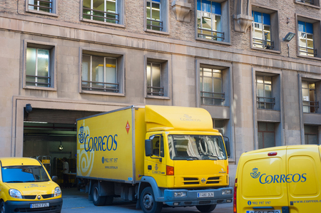 Yellow Correos post trucks in the street of Baecelona, Spain