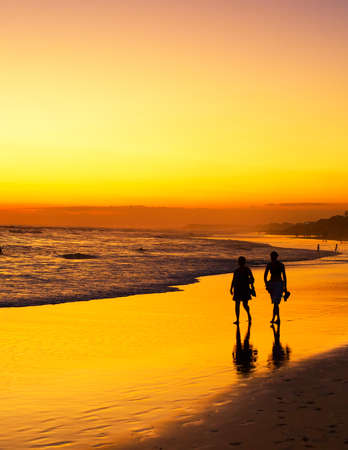 People walking on the ocean beach at sunset. Silhouette. Bali island, Indonesia